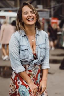 Eine schöne junge frau mit langen haaren mit einem glas kaffee lächelt und lacht.