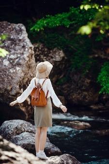 Eine schöne junge frau mit roten haaren, in einem hut und mit einem rucksack in der nähe eines lauten flusses im wald.