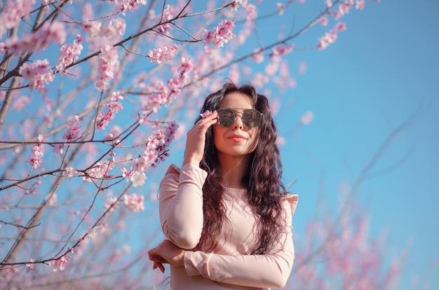 Eine schöne junge frau mit verspiegelter sonnenbrille nahe einem blühenden frühlingskirschblütenbaum. die idee und das konzept von erneuerung, selbstfürsorge, gesundheit und glück