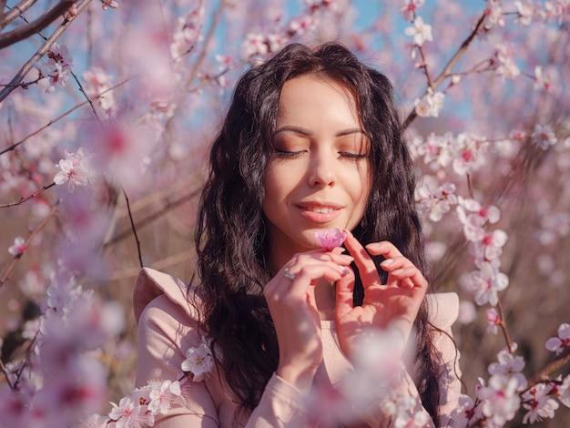 Eine schöne junge frau nahe einem blühenden frühlingskirschblütenbaum. die idee und das konzept von erneuerung, selbstfürsorge und glück