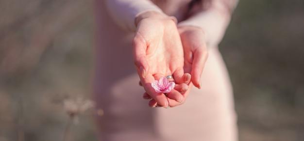 Eine schöne junge frau nahe einem blühenden frühlingskirschblütenbaum. die idee und das konzept von erneuerung, selbstpflege, gesundheit und glück, nahaufnahmen