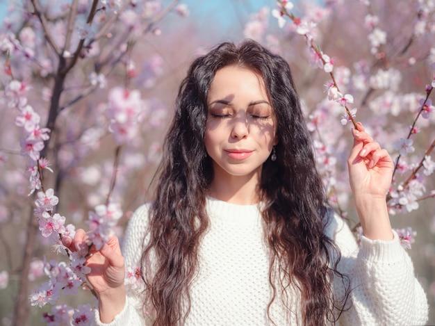 Eine schöne junge frau nahe einem blühenden frühlingskirschblütenbaum. die idee und das konzept von selbstfürsorge, gesundheit und glück