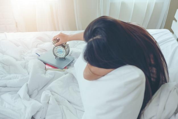 Eine schöne junge frau schläft und ein wecker im schlafzimmer zu hause.