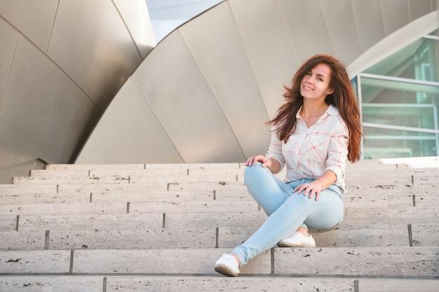 Eine schöne junge frau sitzt auf den stufen der walt disney concert hall los angeles