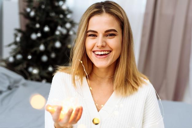 Eine schöne junge frau sitzt auf einem bett vor dem hintergrund eines weihnachtsbaums, hält eine girlande in den händen und lächelt in die kamera. silvester und weihnachten zu hause feiern