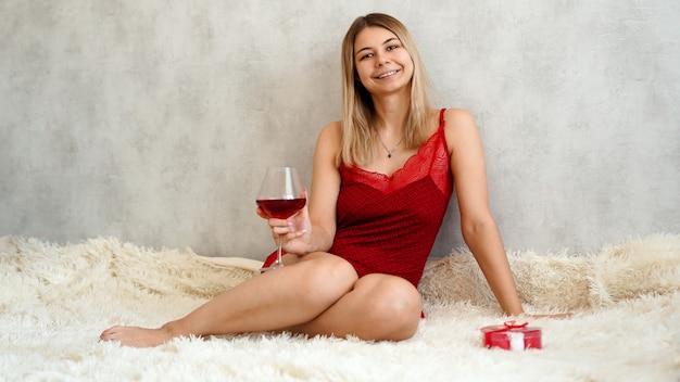 Eine schöne junge frau sitzt in roter unterwäsche auf einem weißen plaid mit wein in der hand. valentinstag morgen