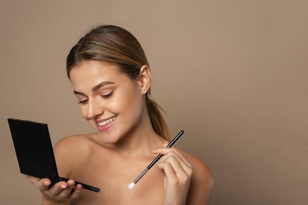Eine schöne junge frau trägt aus einer lidschatten-palette einen braunen lidschatten auf ihre augen auf. studioporträt einer frau, die alltägliches make-up tut.