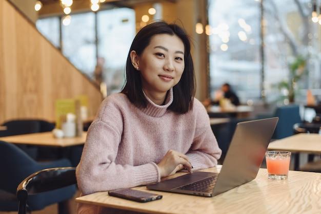 Eine schöne junge frau von asiatischem aussehen arbeitet an einem laptop in einem café. konzept der arbeit außerhalb des hauses, freiberuflich.
