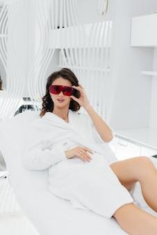 Eine schöne junge frau wird in einem spa-salon mit moderner ausrüstung einer laser-haarentfernung unterzogen.