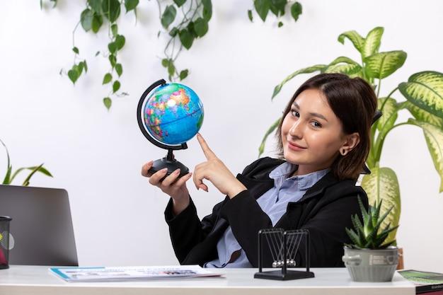Eine schöne junge geschäftsfrau der vorderansicht in der schwarzen jacke und im blauen hemd, die kleinen globus beobachten, der vor dem jobbüro des tischgeschäfts lächelt
