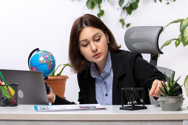 Eine schöne junge geschäftsfrau der vorderansicht in der schwarzen jacke und im blauen hemd, die kleinen globus vor dem jobbüro des tischgeschäfts beobachten