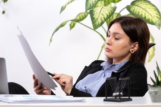 Eine schöne junge geschäftsfrau der vorderansicht in der schwarzen jacke und im blauen hemd, die mit dokumenten vor dem jobbüro des tischgeschäfts arbeiten