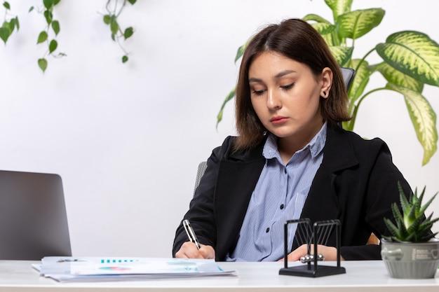 Eine schöne junge geschäftsfrau der vorderansicht in der schwarzen jacke und im blauen hemd, die mit laptop arbeiten, der die notizen vor dem jobbüro des tischgeschäfts aufschreibt