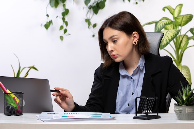 Eine schöne junge geschäftsfrau der vorderansicht in der schwarzen jacke und im blauen hemd, die mit laptop vor dem jobbüro des tischgeschäfts arbeiten