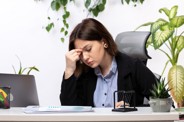 Eine schöne junge geschäftsfrau der vorderansicht in der schwarzen jacke und im blauen hemd, die sich vor dem jobbüro des tischgeschäfts krank fühlen