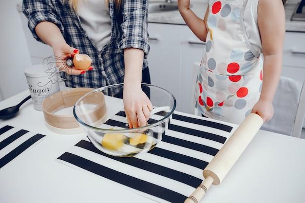 Eine schöne junge mutter mit ihrer kleinen tochter kocht in der küche zu hause