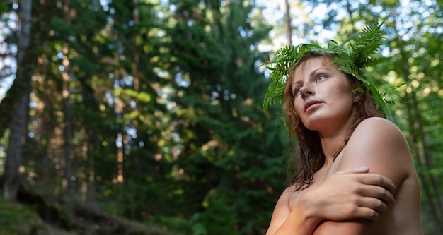 Eine schöne junge nackte frau mit farnkranz auf ihrem kopf, die natur im waldfluss genießt