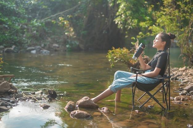 Eine schöne junge reisende frau genießt mit der natur kaffee am morgen über see, entspannung, campingurlaub und reisekonzept zu trinken