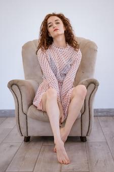 Eine schöne junge schlanke rothaarige frau liegt auf einem stuhl und schaut auf