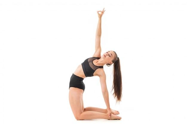 Eine schöne junge turnerin mit dunklen langen haaren wärmt sich auf und streckt ihre muskeln.