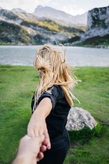 Eine schöne kaukasische blonde frau hält die hand eines mannes in einer gebirgslandschaft mit see