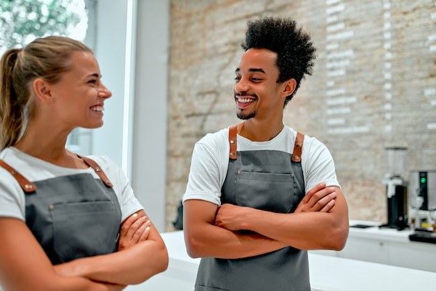 Eine schöne kaukasische frau und ein attraktiver afrikanischer barista in einer schürzenuniform stehen mit verschränkten armen in einem café.