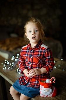 Eine schöne kleine blondine in einem traditionellen karierten hemd