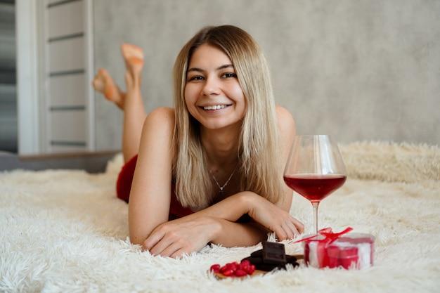 Eine schöne lächelnde blondine liegt im bett. valentinstag morgen. ein glas wein, schokolade, süßigkeiten und ein geschenk neben dem mädchen. glücklicher morgen in der liebe
