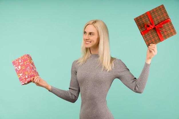 Eine schöne lächelnde frau in einem grauen kleid halten in den geschenken der hände