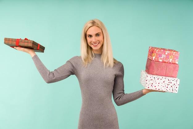 Eine schöne lächelnde frau in einem grauen kleid, in den händen geschenke halten. feier von weihnachten oder neujahr auf blauem hintergrund