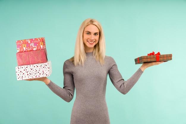 Eine schöne lächelnde frau in einem grauen kleid, in den händen geschenke halten
