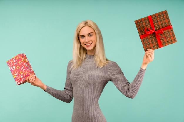 Eine schöne lächelnde frau in einem grauen kleid, in den händen geschenke halten.