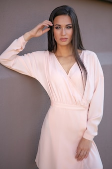 Eine schöne luxuriöse brünette in einem hellbeigen kleid
