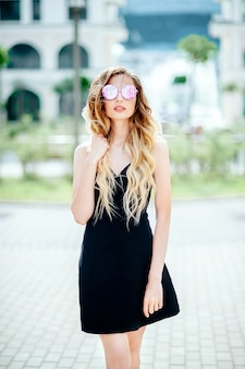 Eine schöne modefrau in einem schwarzen kleid auf einer stadtstraße. natürliches sonnenlicht