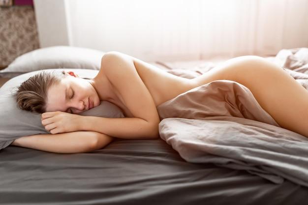 Eine schöne, nackte frau schläft im licht der aufgehenden sonne in ihrem schlafzimmer zu hause und lächelt aus guten träumen. gesunder schlaf.