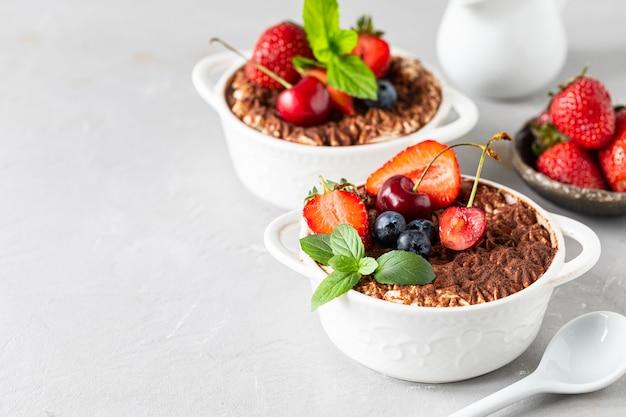 Eine schöne portionierte portion italienisches tiramisu-dessert, garniert mit erdbeeren, kirschen und minze auf weißem grund. kopieren sie platz für ihren text.