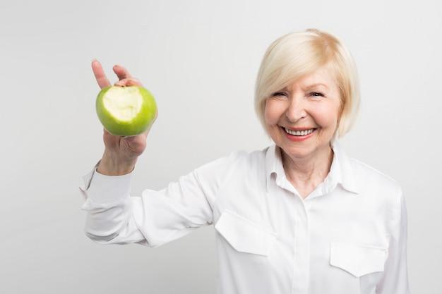 Eine schöne reife frau, die einen gebissenen grünen apfel in der rechten hand hält. sie will zeigen, dass sie gute und kräftige zähne hat.