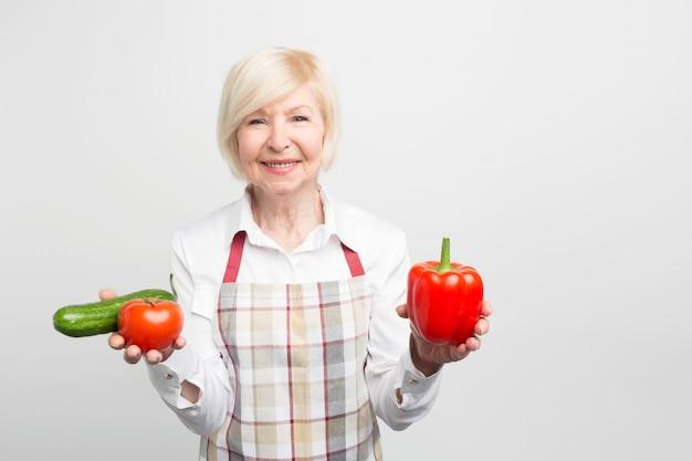Eine schöne reife frau, die einen roten pfeffer in der linken hand und sowohl tomate als auch gurke in der rechten hand hält. sie kocht gerne verschiedene salate oder backt gemüse.