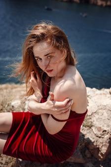 Eine schöne rothaarige frau im roten kleid sitzt auf einem felsen mit herrlichem blick auf die seelandschaft. sommernachmittag genuss von freiheit und einsamkeit