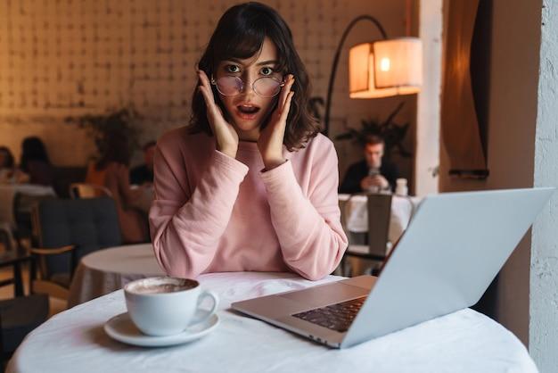Eine schöne schockierte frau drinnen im café mit laptop-computer.