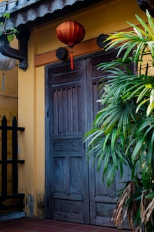 Eine schöne schwarze holztür an einer gelben wand mit chinesischen laternen. antike stadt hoi an. vietnam.