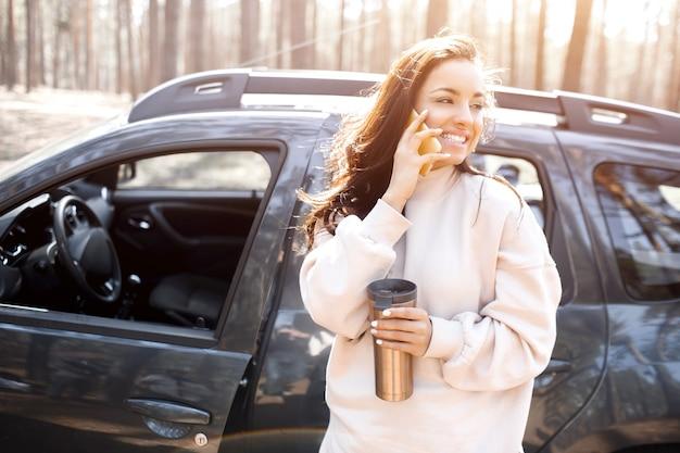 Eine schöne schwarzhaarige junge frau steht in der nähe eines autos in einem wald oder park. weibliche models fahren mit einem crossover aus der stadt. sie spricht am telefon oder smartphone und hält eine thermoskanne