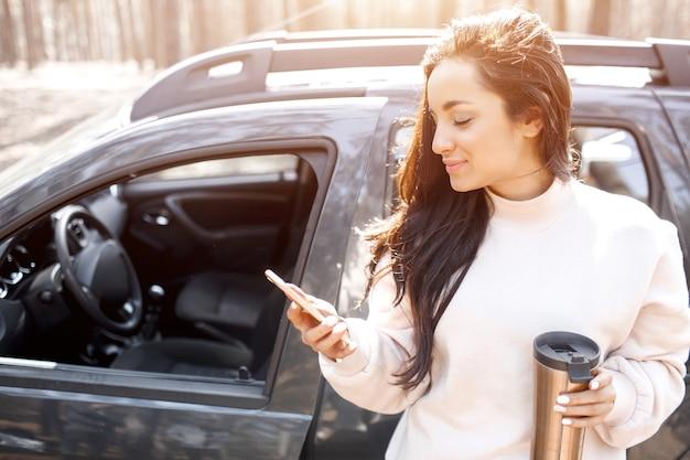 Eine schöne schwarzhaarige junge frau steht in der nähe eines autos in einem wald oder park. weibliche models fahren mit einem crossover aus der stadt. sie spricht am telefon oder smartphone