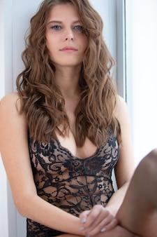 Eine schöne sexy dame in einem eleganten schwarzen body schaut mit ihren blauen augen in einem romantischen stimmungsporträt in die kamera