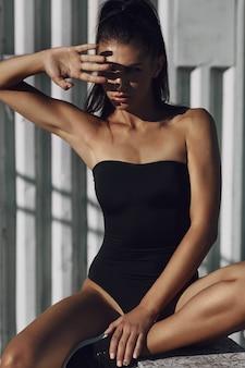 Eine schöne sexy erstaunliche junge frau in einem schwarzen badeanzug, der am strand aufwirft. langes haar, schwarzer bikini, mode, roter faden