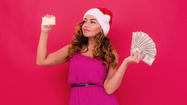 Eine schöne sexy frau in einem hut des neuen jahres, geld und kreditkarte in den händen halten. weihnachts- oder neujahrsfeier