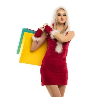Eine schöne sexy frau in einem neujahrskleid, halten in den händen einkaufstaschen lokalisiert auf weiß. weihnachtsfeier oder neujahrsverkauf