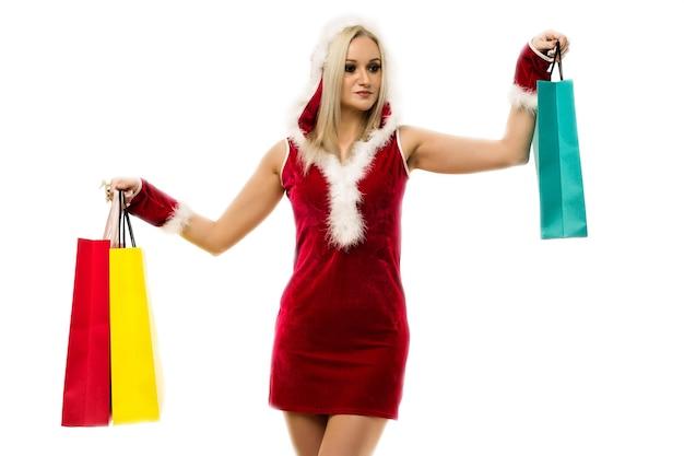 Eine schöne sexy frau in einem neujahrskleid, in den händen einkaufstaschen halten