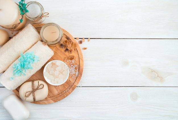 Eine schöne spa-komposition mit einem handtuch, kerzen, blumen und seife auf einem brett auf einem weißen hintergrund.
