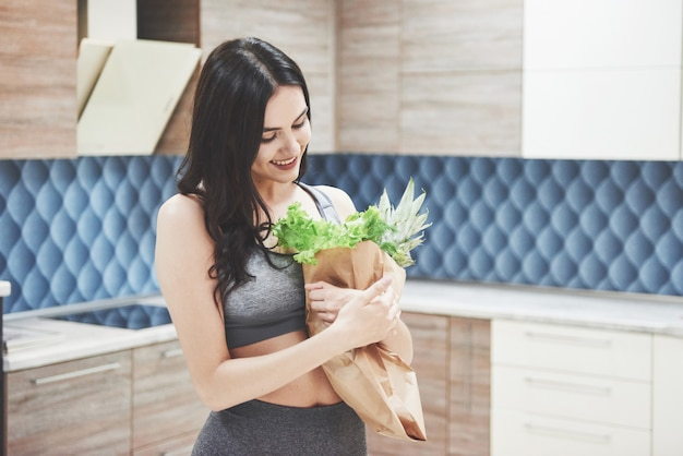 Eine schöne sportfrau mit frischen obst und gemüse in der küche